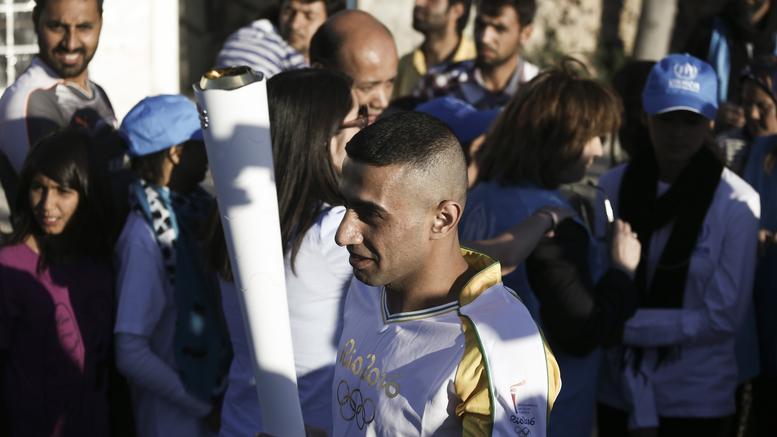 Η Ολυμπιακή Φλόγα στα χέρια ενός πρόσφυγα στον Ελαιώνα